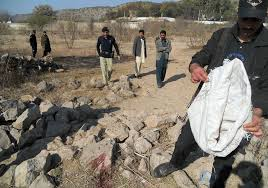 Police investigate the area where Aitzaz had wrestled the suicide bomber to the ground and where both died in the explosion.